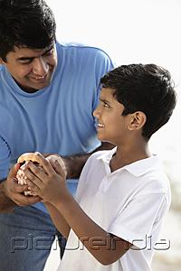PictureIndia - Father and son holding sea shell and smiling
