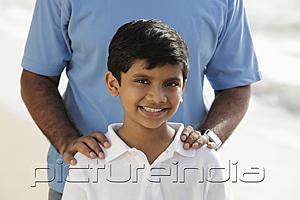 PictureIndia - Cropped shot of father's hands on smiling son's shoulders