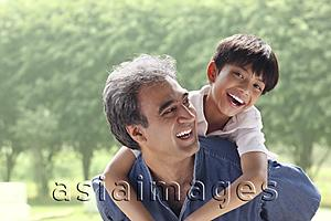 Asia Images Group - Father with son on his back, son smiling at camera