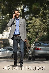 Asia Images Group - man on phone walking with briefcase