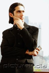 PictureIndia - Businessman with arms crossed and hand on chin, looking away