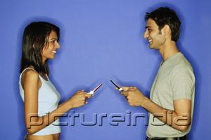 PictureIndia - Couple face to face, holding mobile phones
