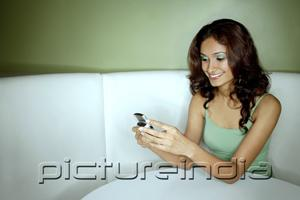 PictureIndia - Young woman sitting in booth, looking at mobile phone