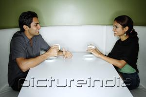 PictureIndia - Couple sitting opposite from each other, having tea