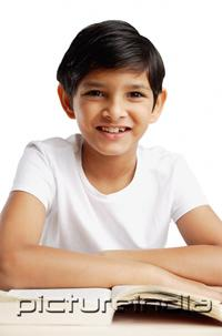 PictureIndia - Boy leaning on book, smiling at camera