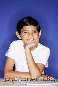PictureIndia - Boy looking at camera, hand on chin