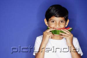 PictureIndia - Boy looking at camera, eating watermelon