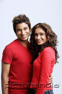 PictureIndia - Couple standing side by side, smiling at camera