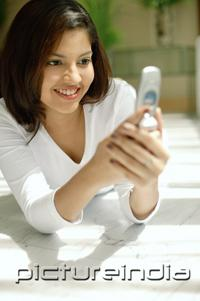 PictureIndia - Woman looking at mobile phone, smiling