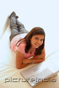 PictureIndia - Woman at home, lying on bed, arms crossed, laptop open in front of her
