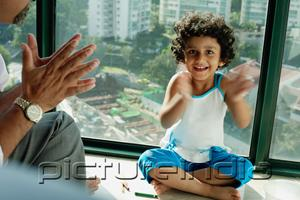 PictureIndia - Girl sitting on floor, clapping hands, smiling at camera, father next to her